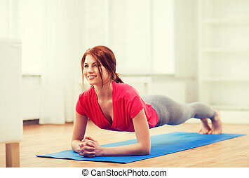 smiling redhead teenage girl doing plank at home