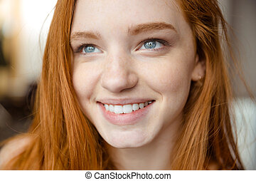 Smiling redhead woman looking up