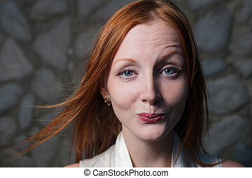 Smiling redhead woman outdoors against stone wall headshot
