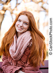 Smiling redhead woman sitting on the bench outdoors -...