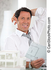 Smiling, relaxed architect looking at plans