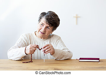 Smiling religious grandmother with rosary sitting at table with bible