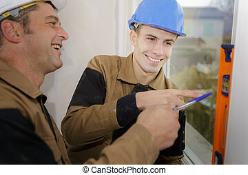 smiling repairman measuring with the help of builder level