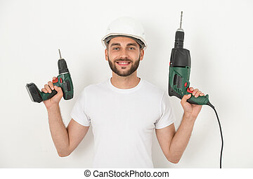 Smiling repairman with power tools