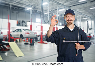 Smiling repairman with tire wrench. - Smiling repairman with...
