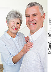 Smiling retired couple looking at camera