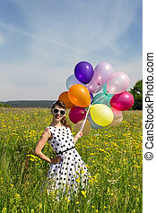Smiling Rockabilly Girl with colorful balloons on the meadow