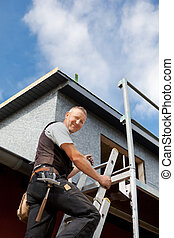 Smiling roofer climbing a ladder at the construction site