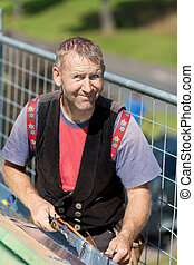Smiling roofer welding the gutter