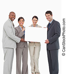 Smiling sales team holding blank sign together against a...