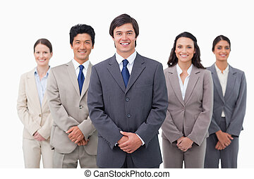Smiling sales team standing against a white background