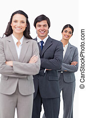Smiling sales team standing together with folded arms
