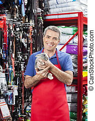 Smiling Salesman Holding Rabbit In Pet Store