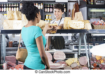 Smiling Salesman Selling Cheese To Female Customer