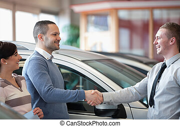 Smiling salesman shaking a customer hand