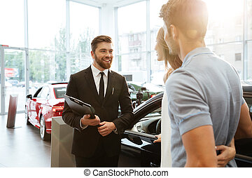 Smiling salesman showing new car to a couple in showroom...