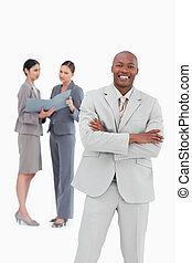 Smiling salesman with arms crossed and co-workers behind him
