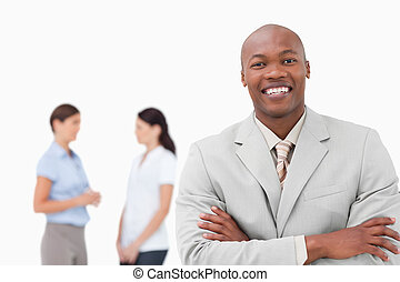 Smiling salesman with arms folded and associates behind him...