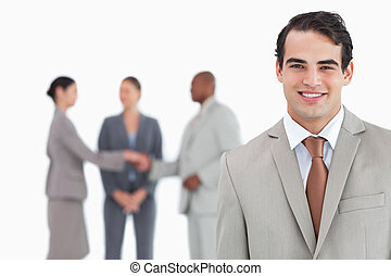 Smiling salesman with businesspeople behind him