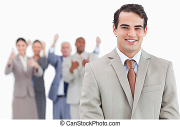 Smiling salesman with cheering team behind him against a white background