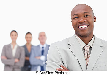 Smiling salesman with team behind him against a white ...