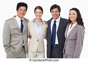 Smiling salespeople standing together against a white...