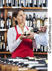 Smiling Saleswoman Giving Wine Bottle To Customer