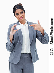 Smiling saleswoman pointing at blank business card