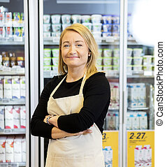 Smiling Saleswoman With Arms Crossed Standing Against Refrigerat