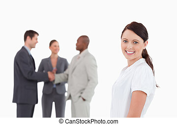 Smiling saleswoman with three colleagues behind her