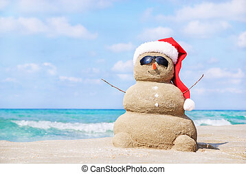 Smiling sandy snowman in red santa hat on the sea beach.