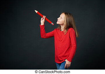 Smiling school age girl holding big pencil and drawing or ...