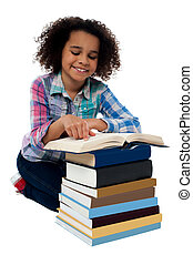 Smiling school girl reading a book