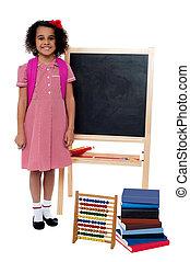 Smiling school girl standing near the blackboard