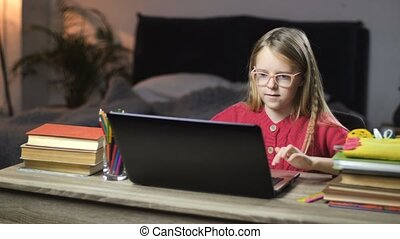 Smiling school girl surfing net on laptop at home