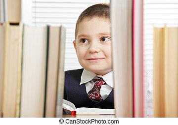Smiling schoolboy behind books