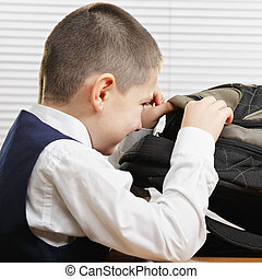 Smiling schoolboy looking into backpack