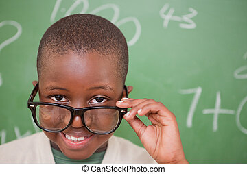 Smiling schoolboy looking over his glasses