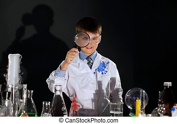 Smiling schoolboy looking through magnifying glass
