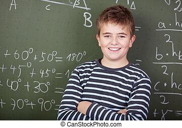Smiling schoolboy standing near blackboard