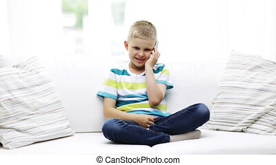 smiling schoolboy with smartphone at home - home, childhood,...