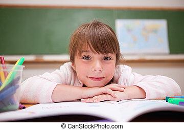 Smiling schoolgirl leaning on a desk