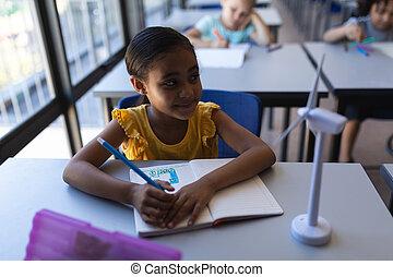 Smiling schoolgirl looking away at desk in classroom
