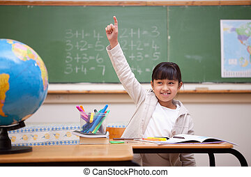 Smiling schoolgirl raising her hand to answer a question