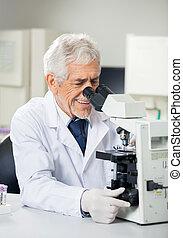 Smiling Scientist Using Microscope In Laboratory