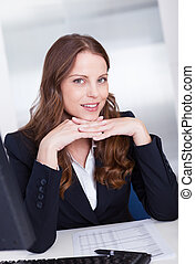 Smiling professional business secretary or personal assistant working at her computer typing on the keyboard