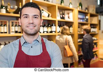 smiling seller man wearing apron in wine store