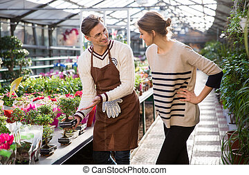 Smiling seller showing small bonsai tree to young woman - ...