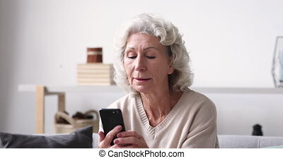 Smiling senior adult grandmother using smartphone sitting on sofa. Happy 70s elder woman holds mobile phone texting message, checking app, reading news at home. Old grandparent learns tech gadget concept