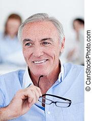 Smiling senior businessman holding glasses
